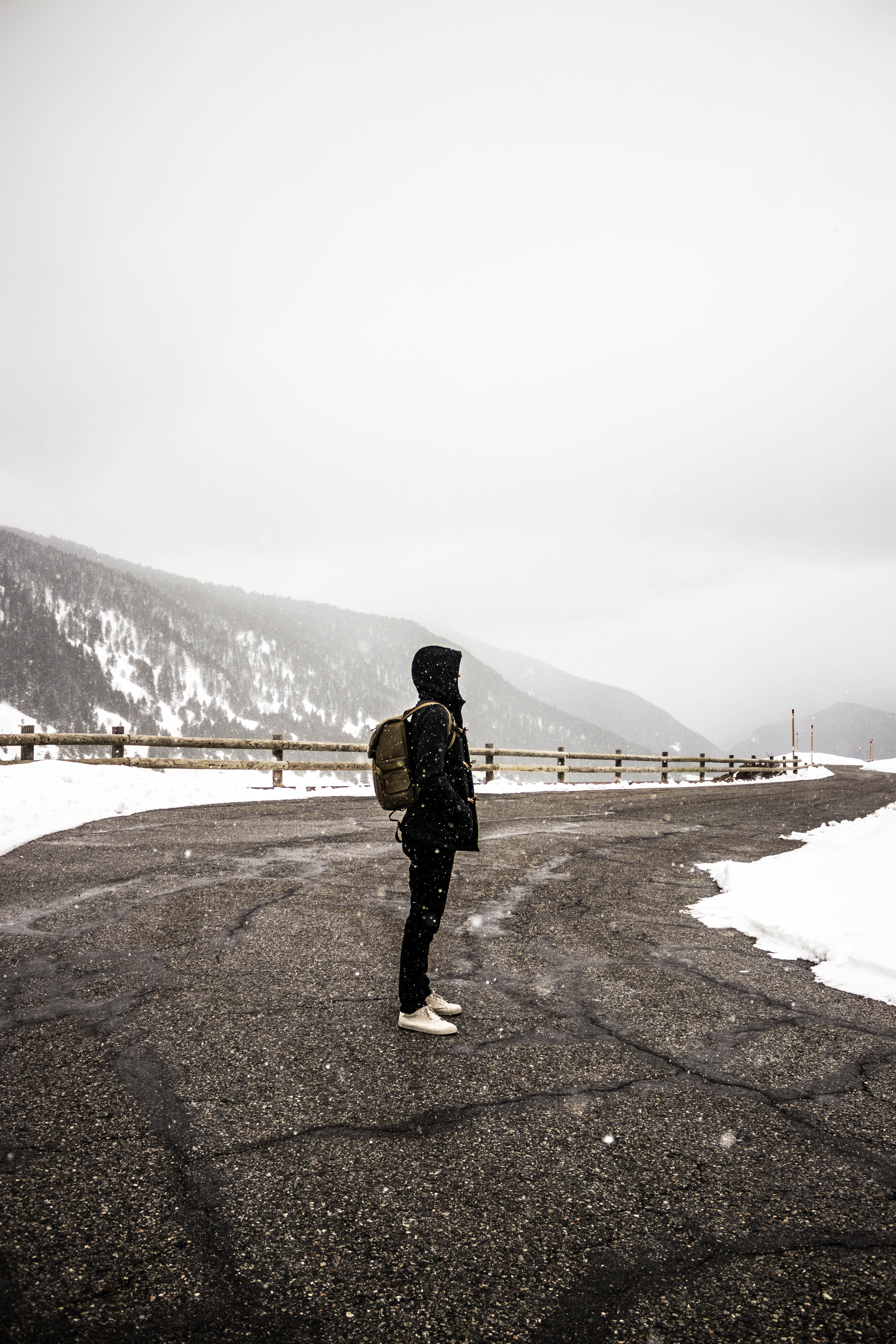 person standing on gray concrete top road near snow