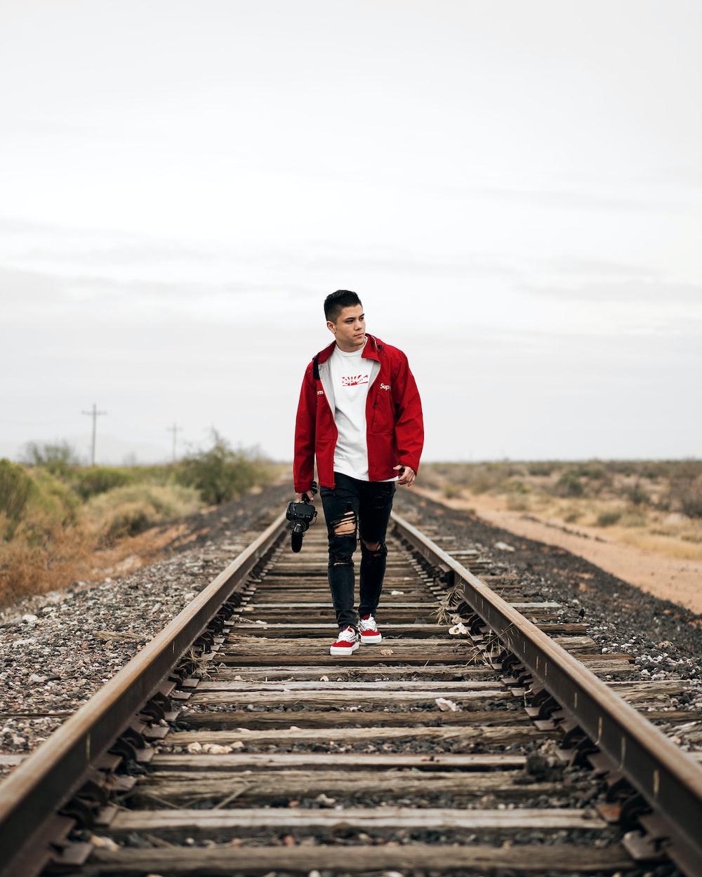 man wearing jacket waking on train rail