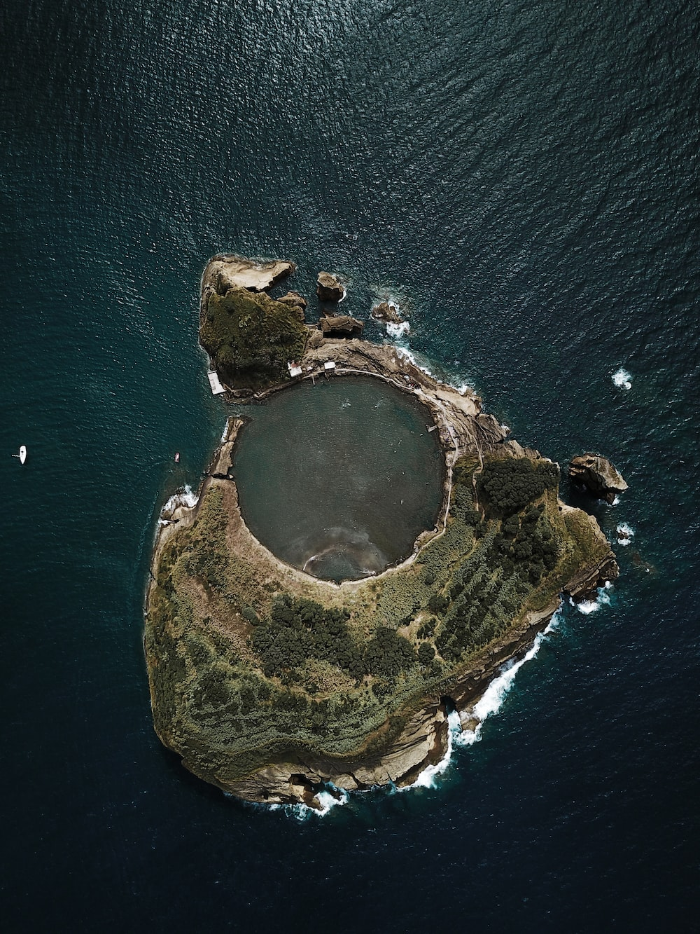 top view photography of island covered with trees surrounded by body of water during daytime