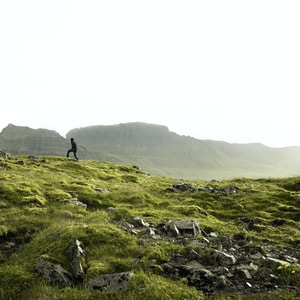 person standing on green grass covered mountain during daytime