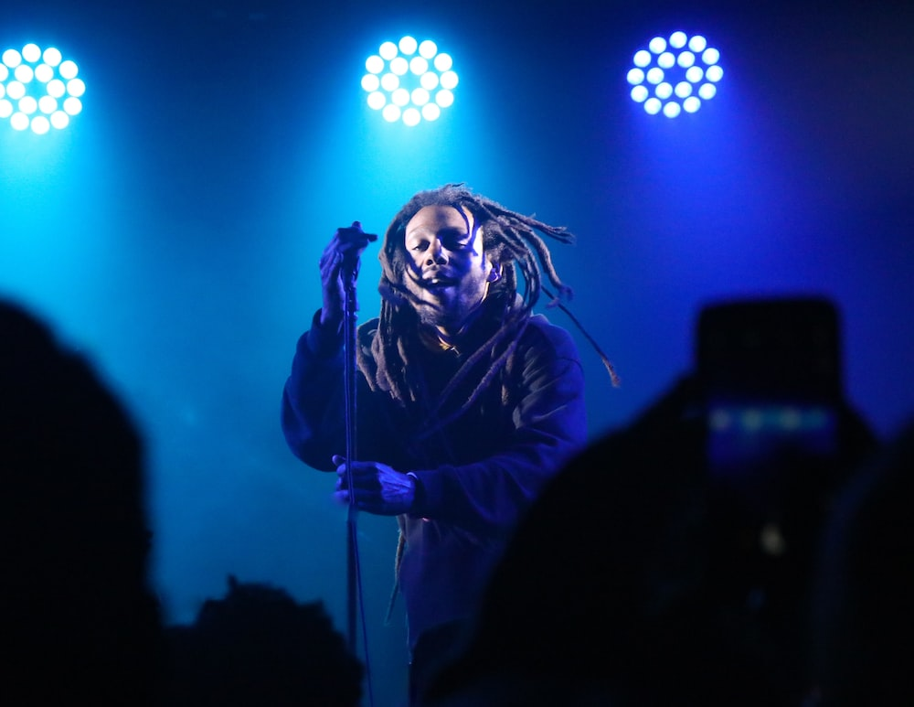 man standing on stage with blue spotlight