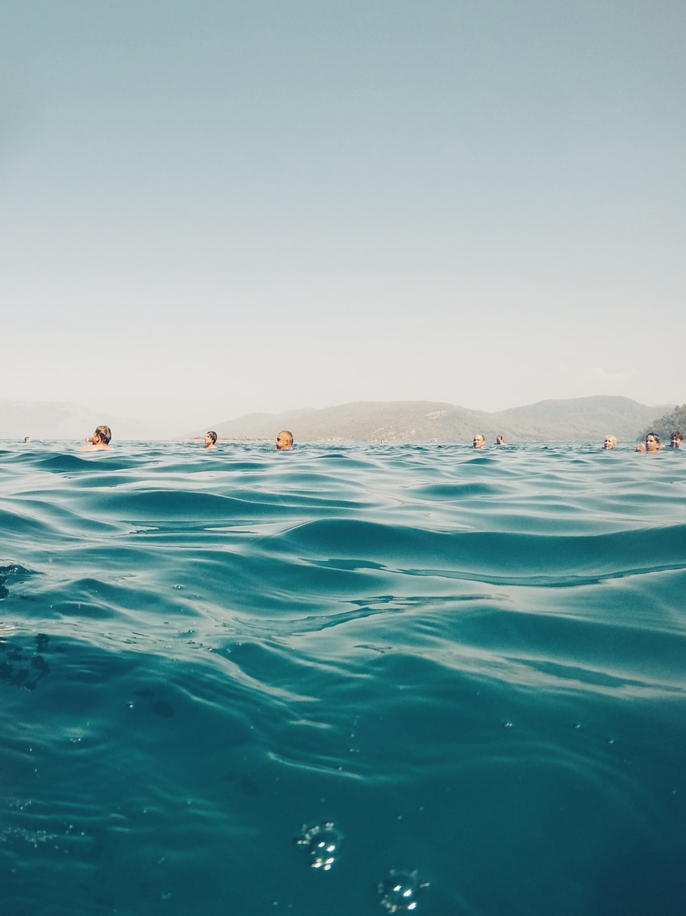 group of people swimming on beach