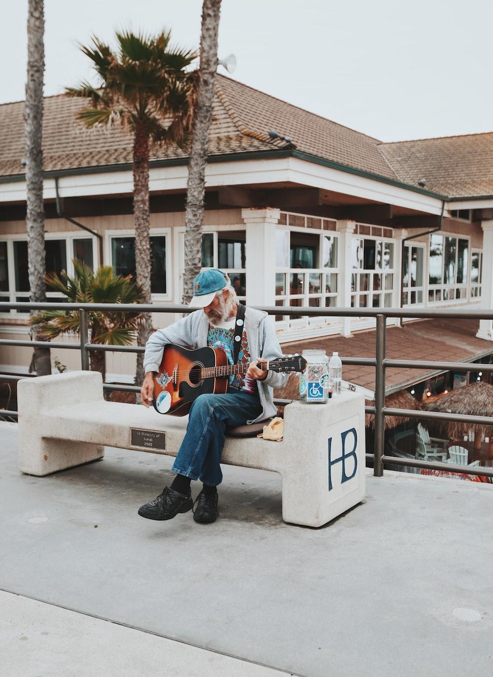 man sitting on outdoor bench playing guitar during daytime