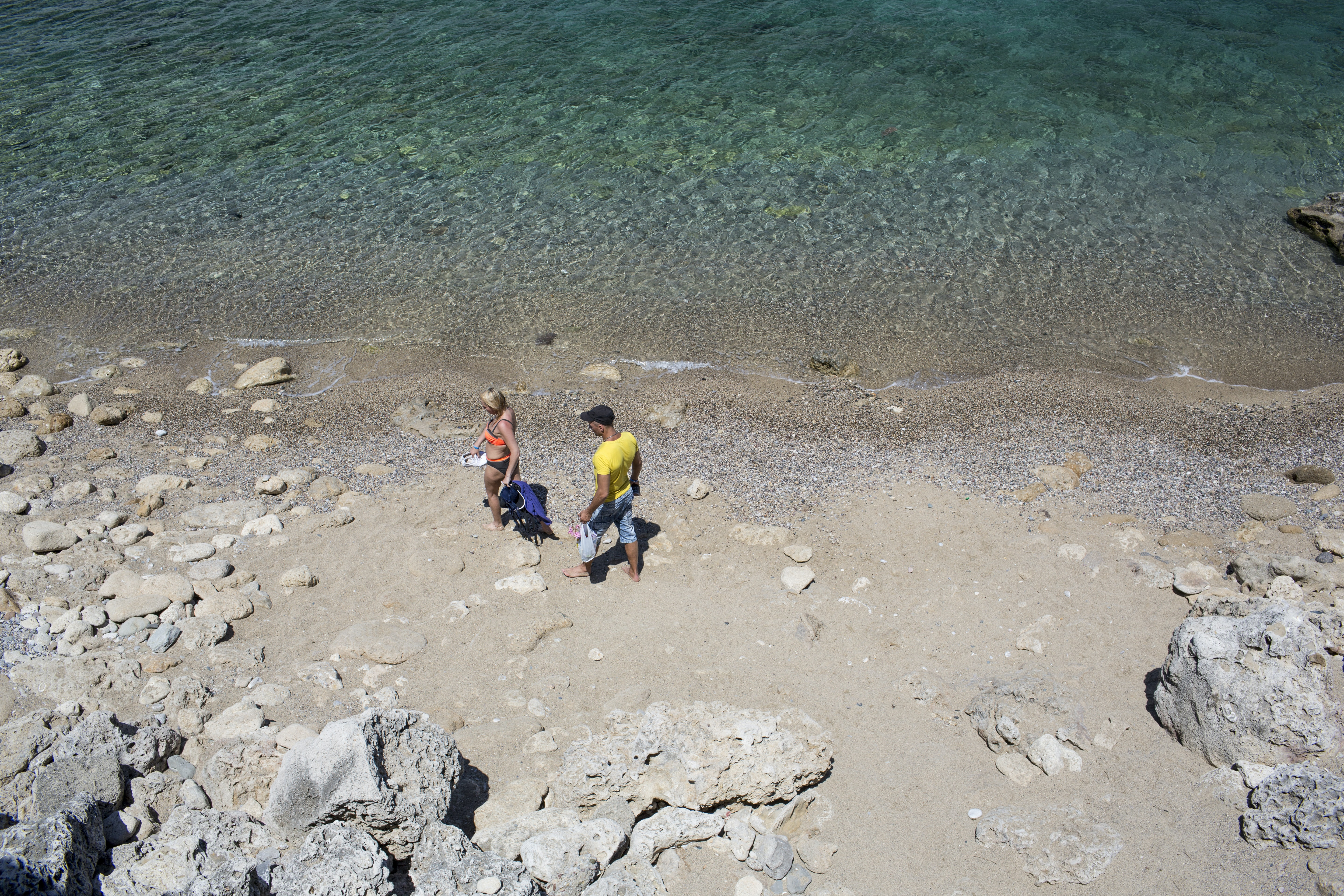 man and woman standing near body of water during daytime