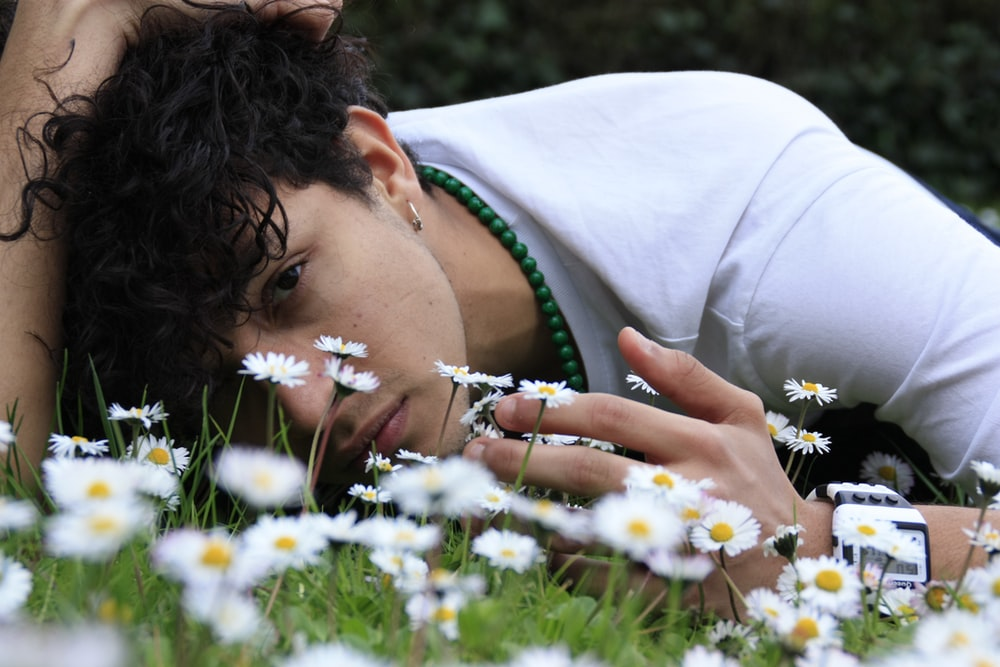man lying down on flower bed