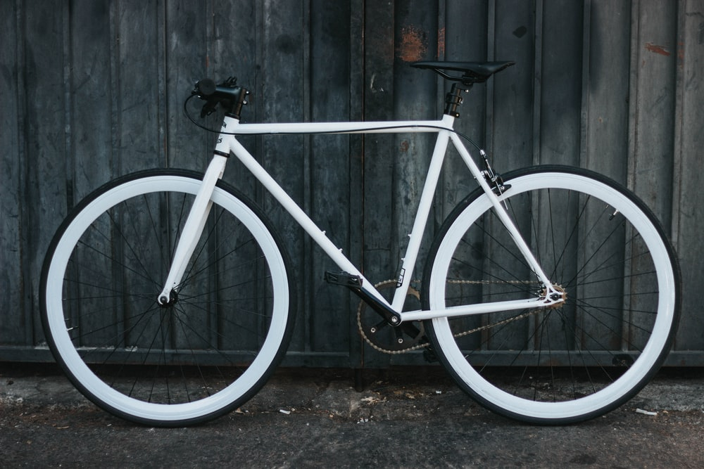 white road bicycle beside gray steel panel