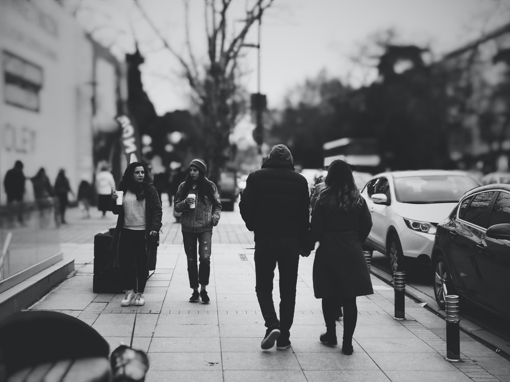 grayscale selective focus photography of people walking on road