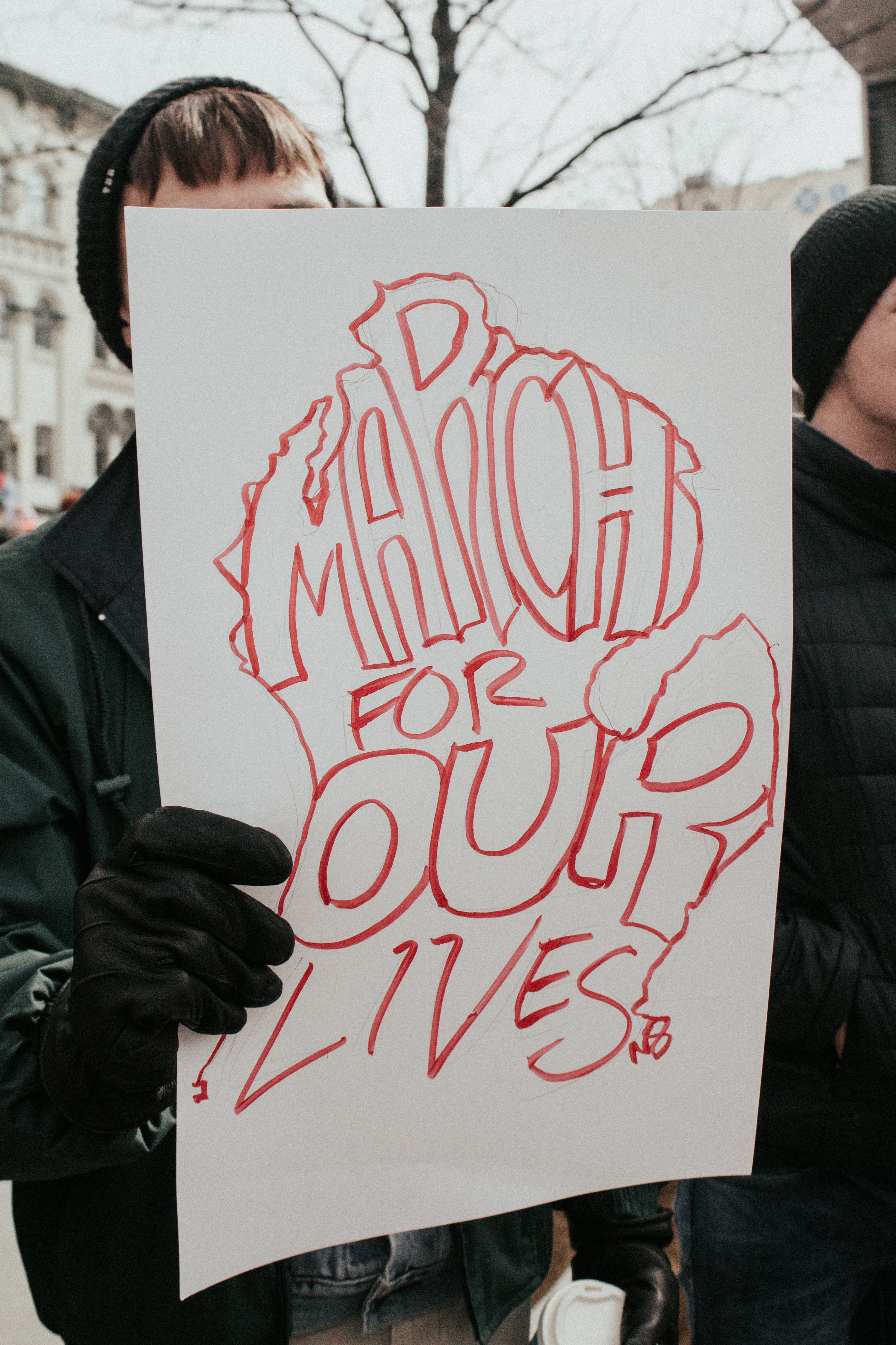 person holding board with march for our lives text