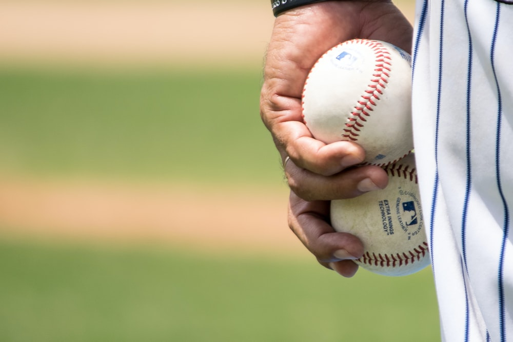 man holding two white baseballs