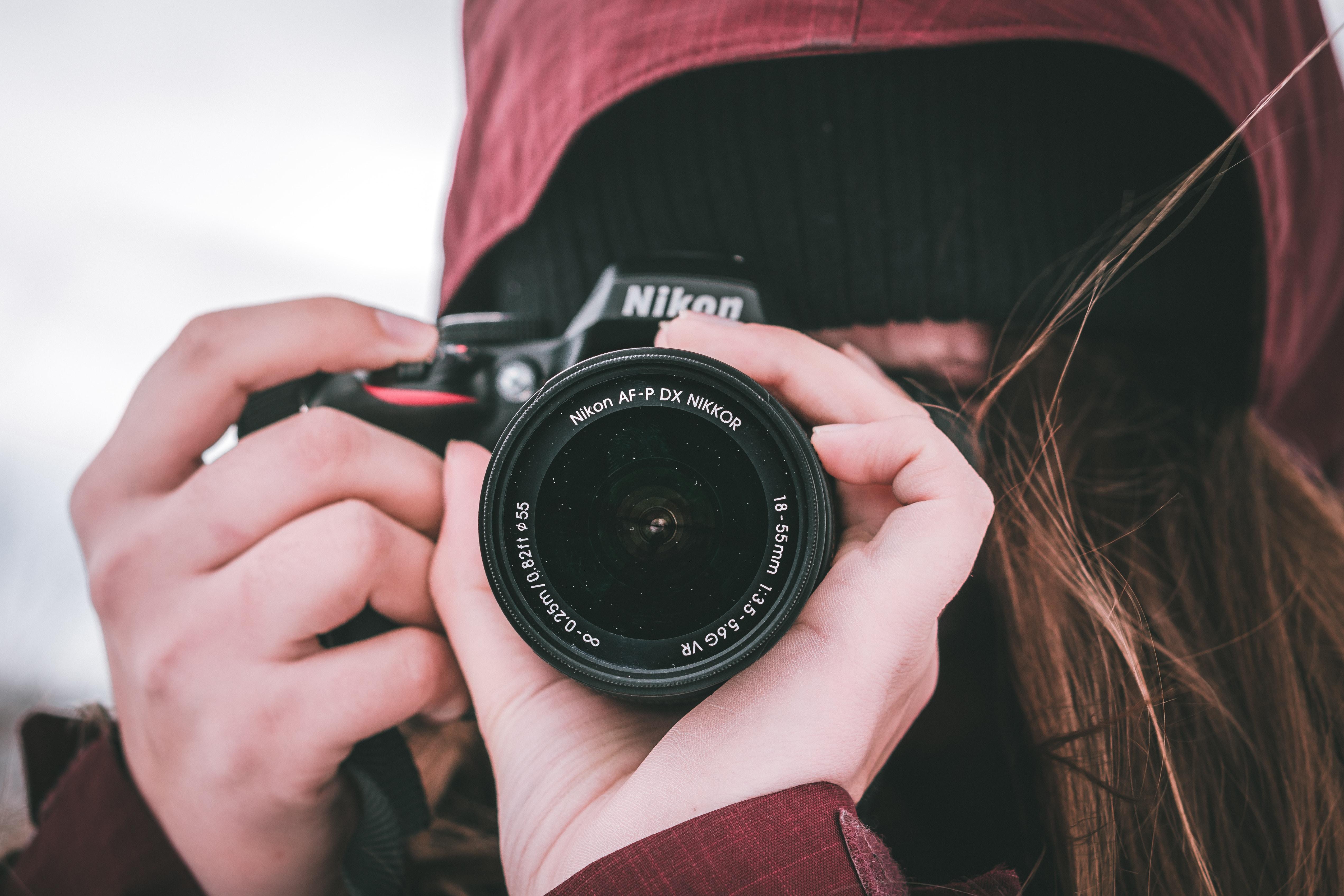 woman holding black Nikon DSLR camera