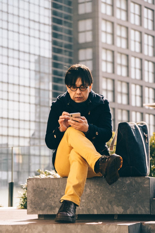 man using smartphone sitting on concrete bench