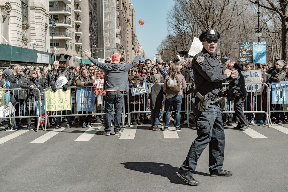 police man standing on road near people watching