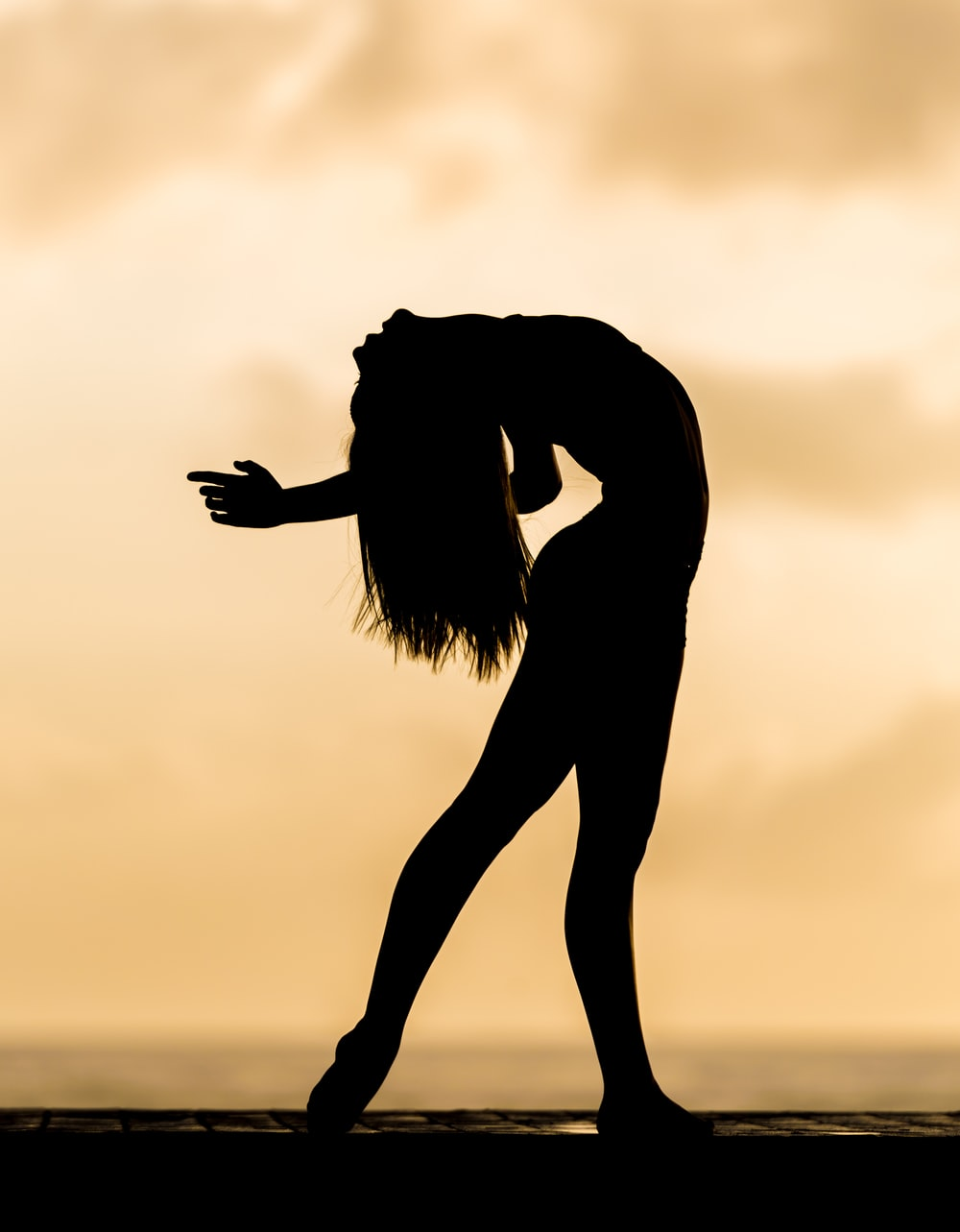 silhouette of bending woman