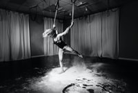 grayscale photography of woman holding rope near curtain