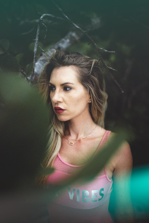 shallow focus photo of woman wearing tank top posing below tree