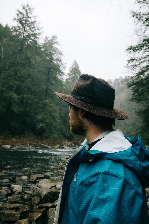 man wearing black hat standing near the river