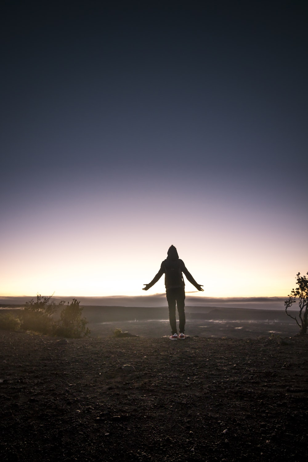 silhouette of person standing on mountain top