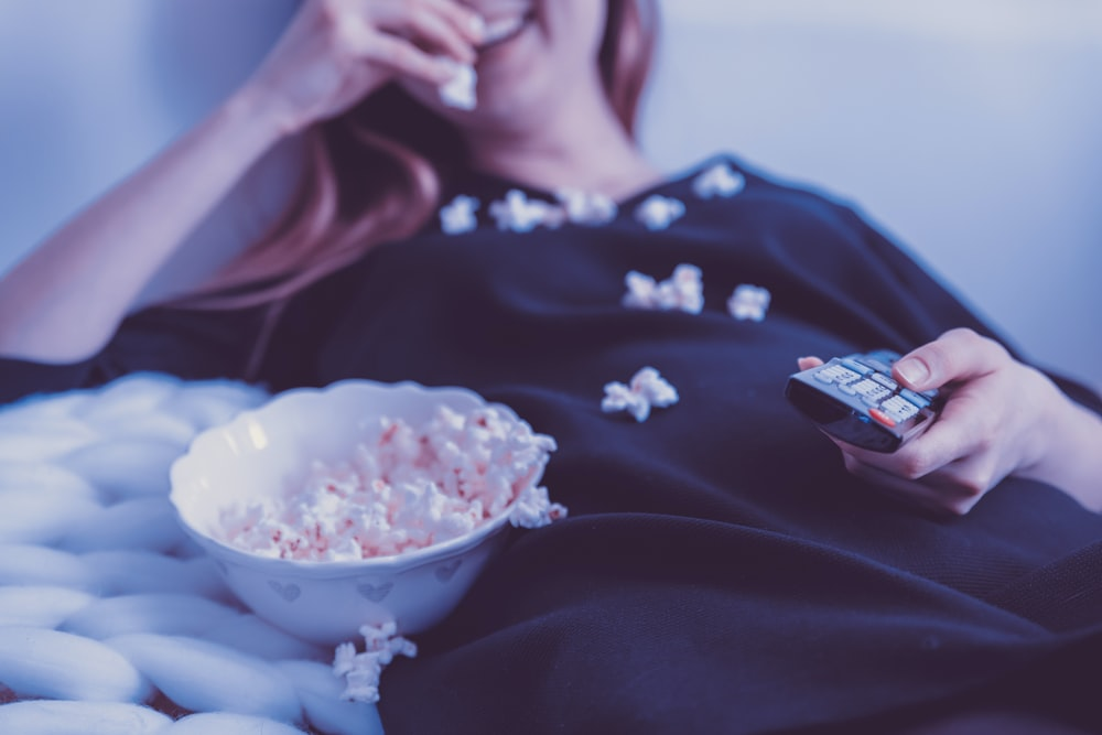 woman lying on bed while eating puff corn