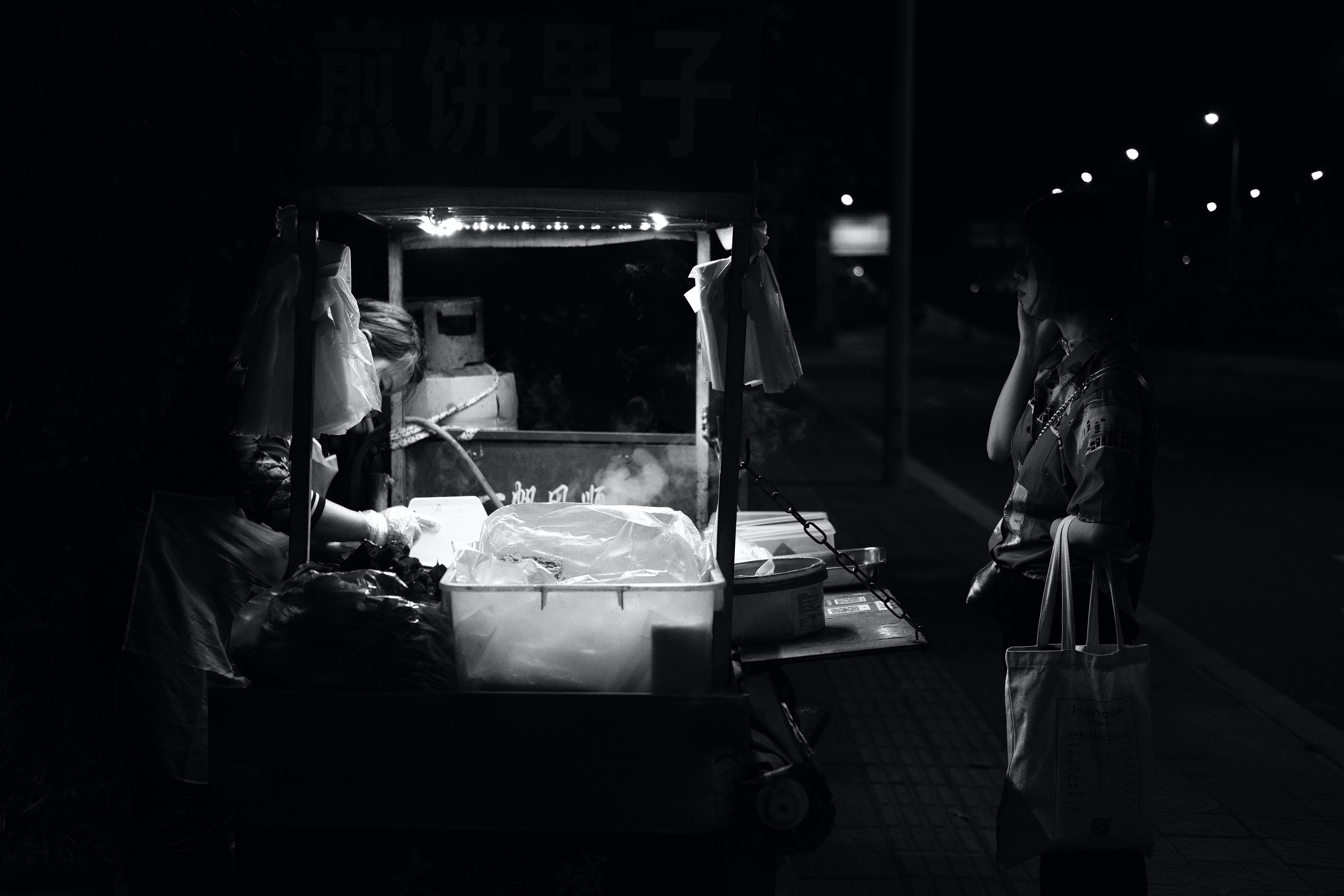 grayscale photo of woman infront of food stall