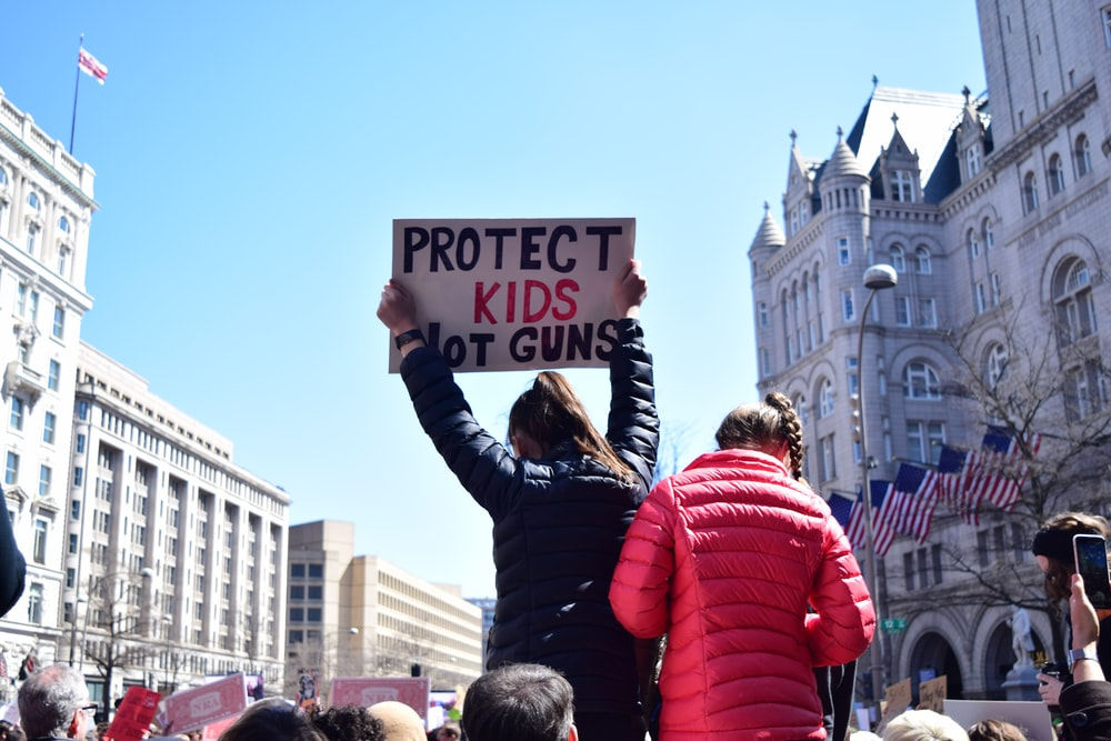 woman in black jacket holding signage panel