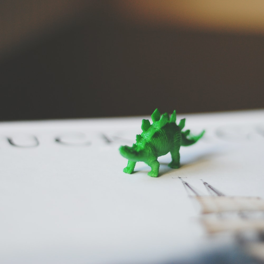 selective focus photography of green dinosaur toy