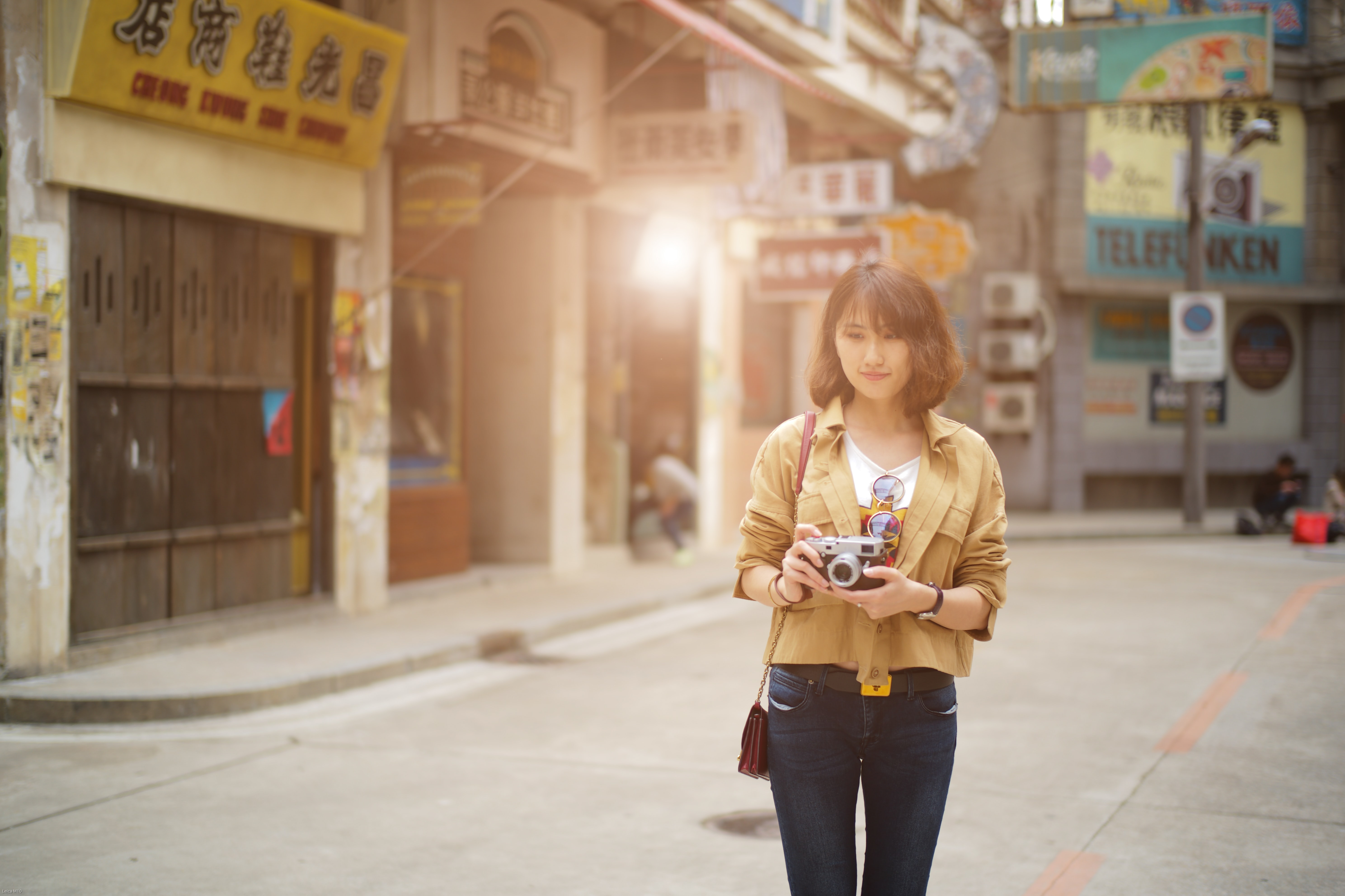standing woman holding camera near stores
