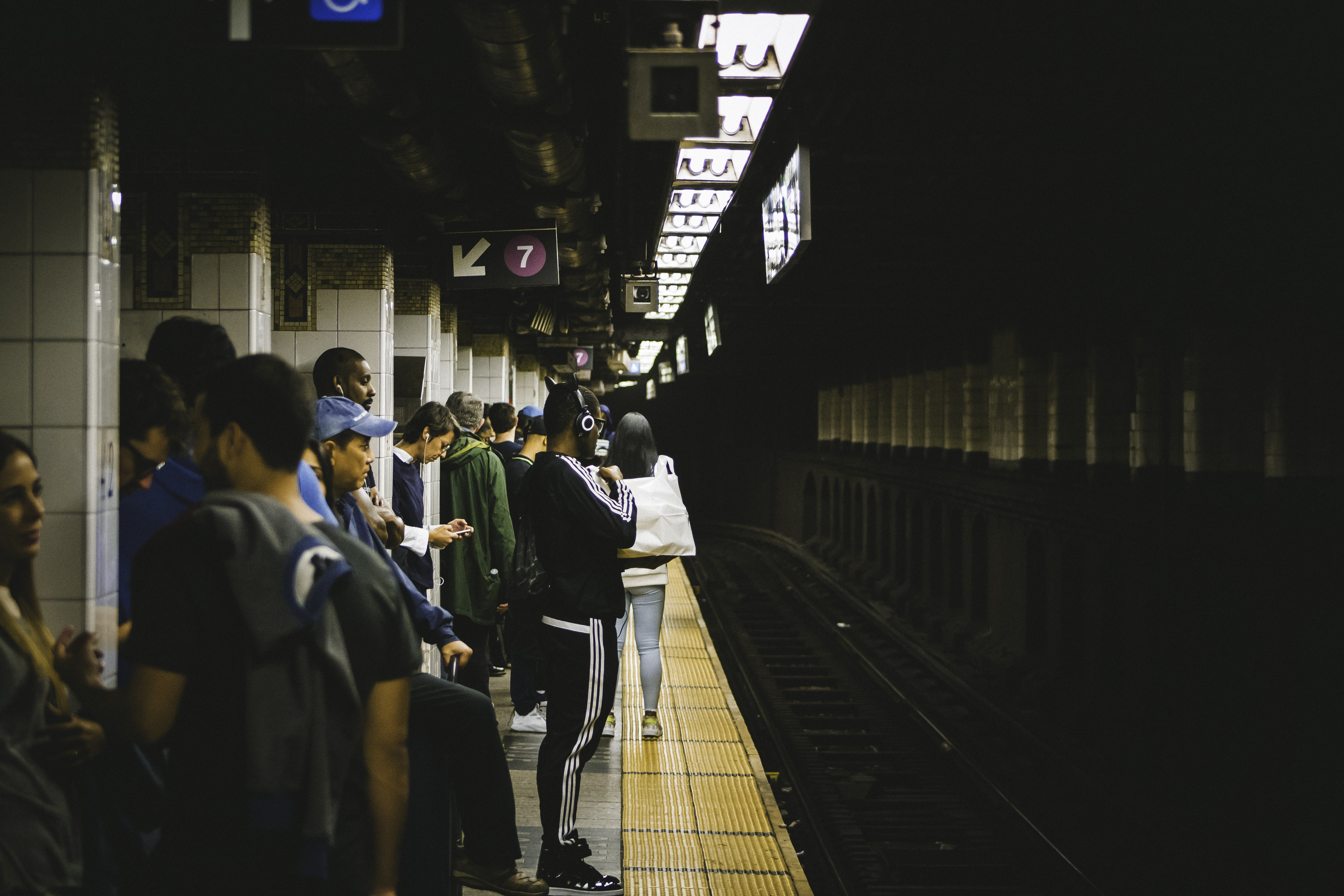 people standing in train station tunnel