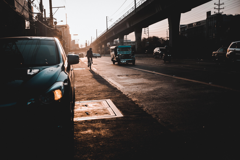 man riding bike behind black SUV near vehicles and bridge during daytime