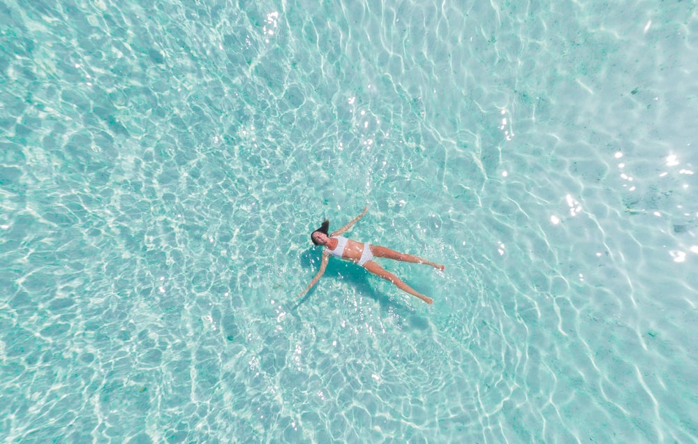 woman swimming on body of water