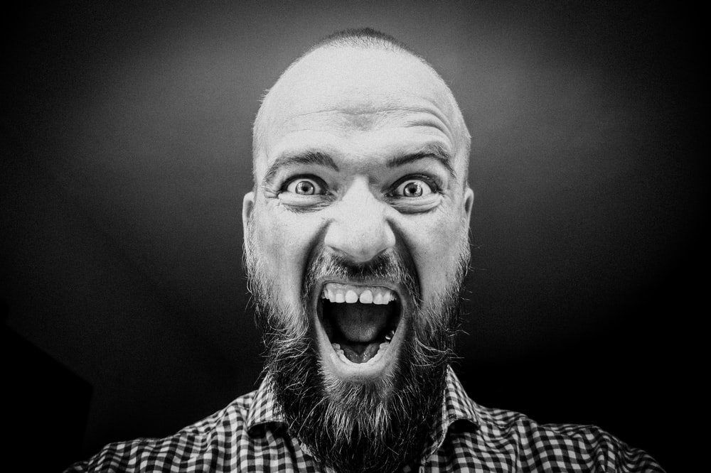 grayscale photography of man opening his mouth