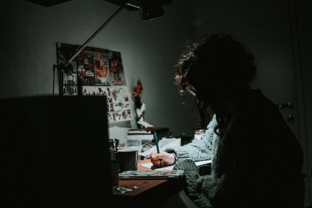 low light photography of woman in gray knit sweatshirt writing on desk