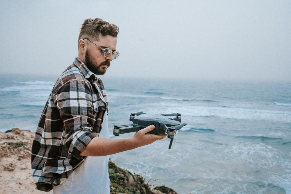 man holding black and brown DJI Mavic Pro drone on his right hand while standing on cliffside with view of sea during daytime photo