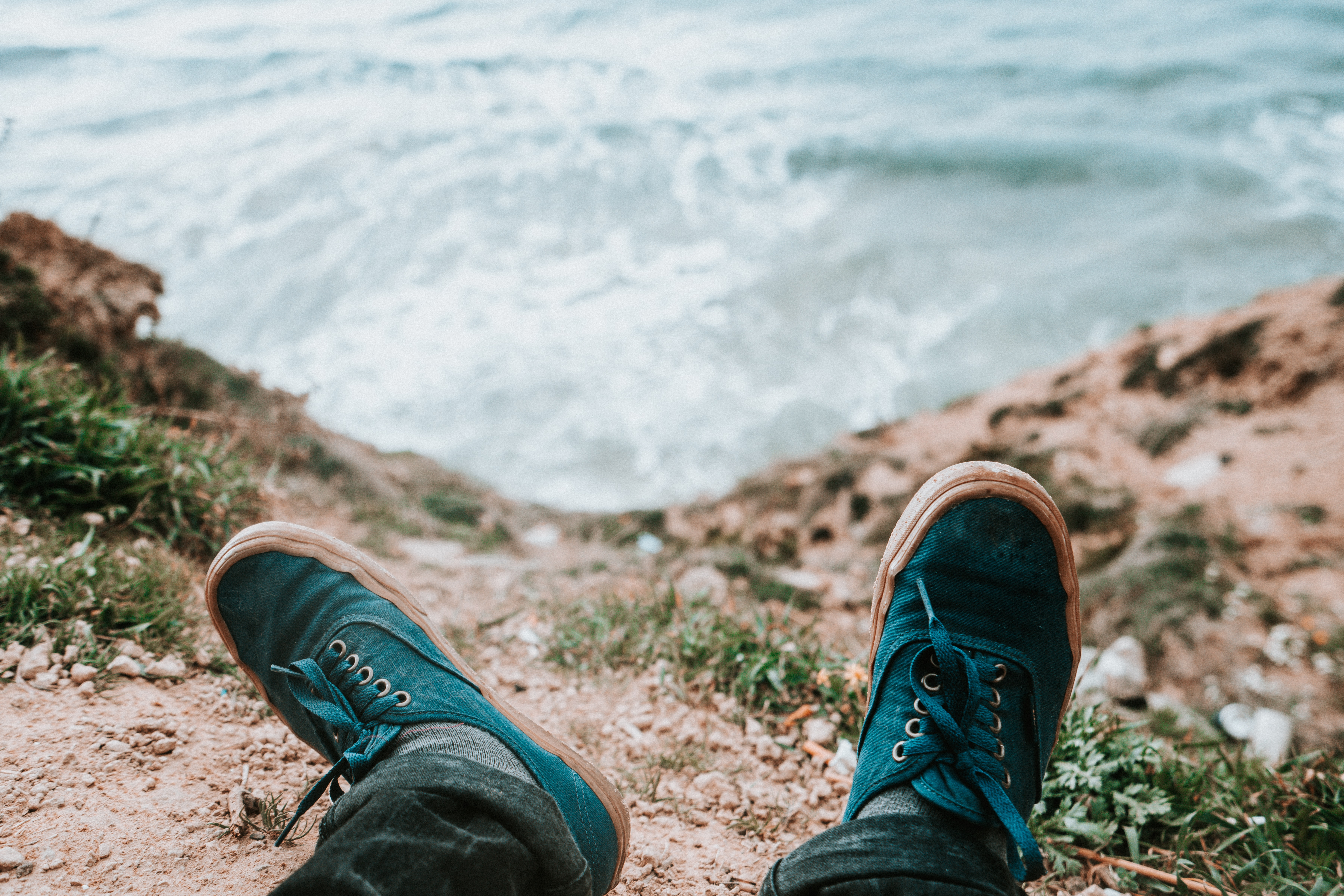 person wearing blue and brown low-top sneakers in front of body of water