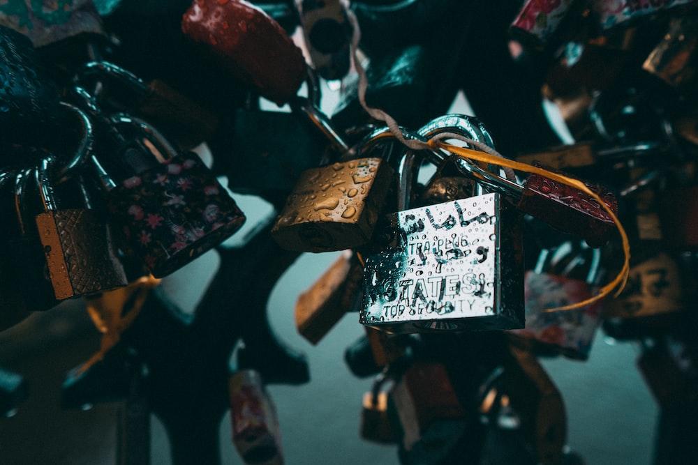 closeup photo of padlocks on metal grill