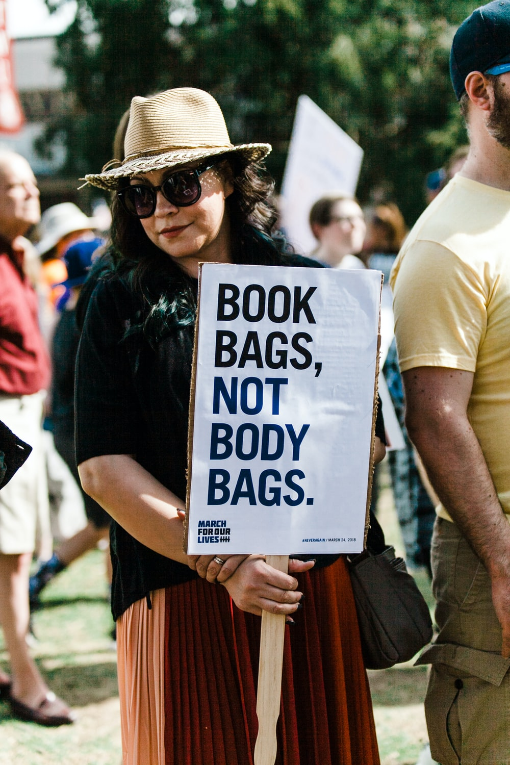 woman holding book bags, not body bags. signboard