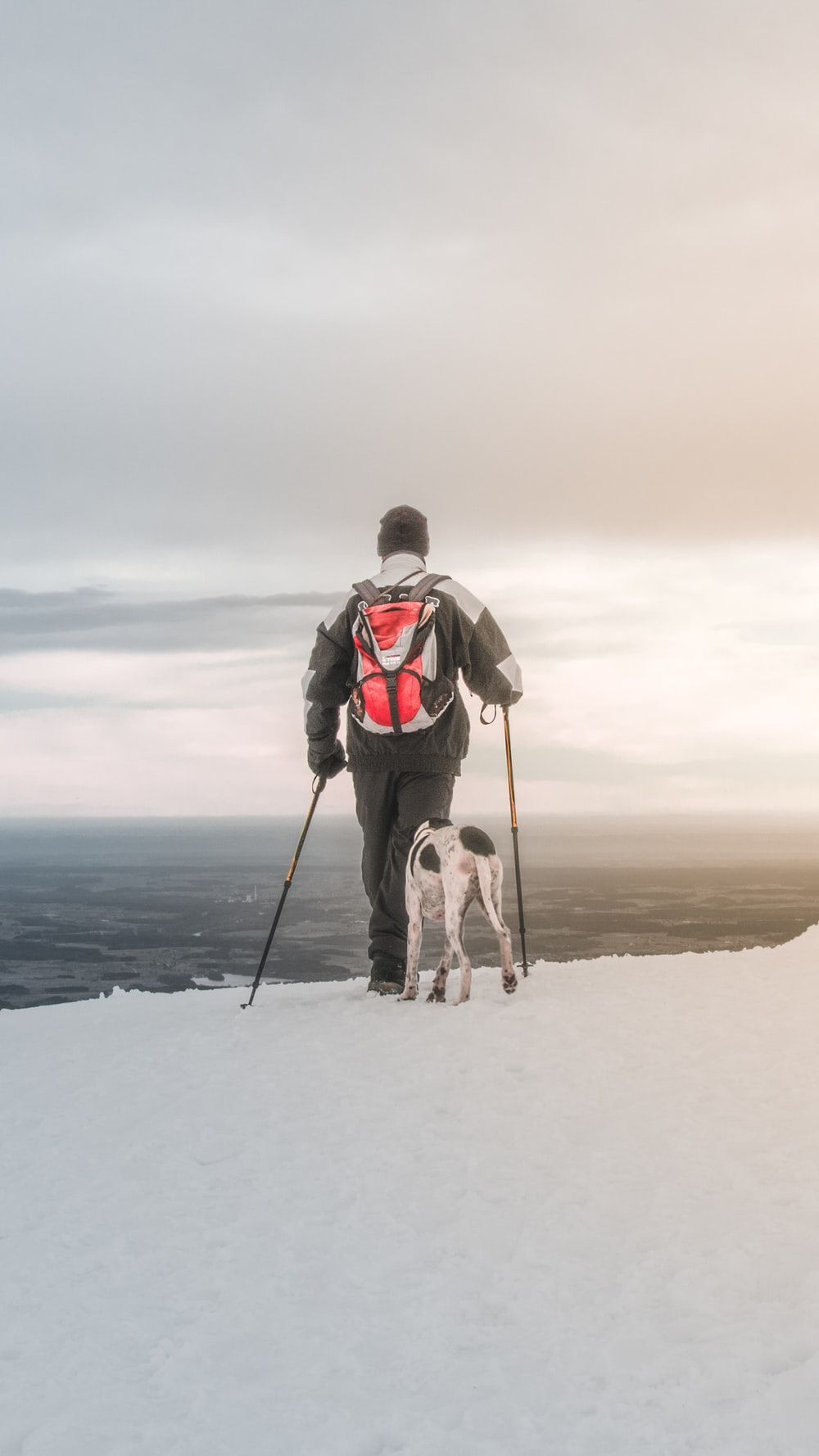 man hiking on frozen ground with dog