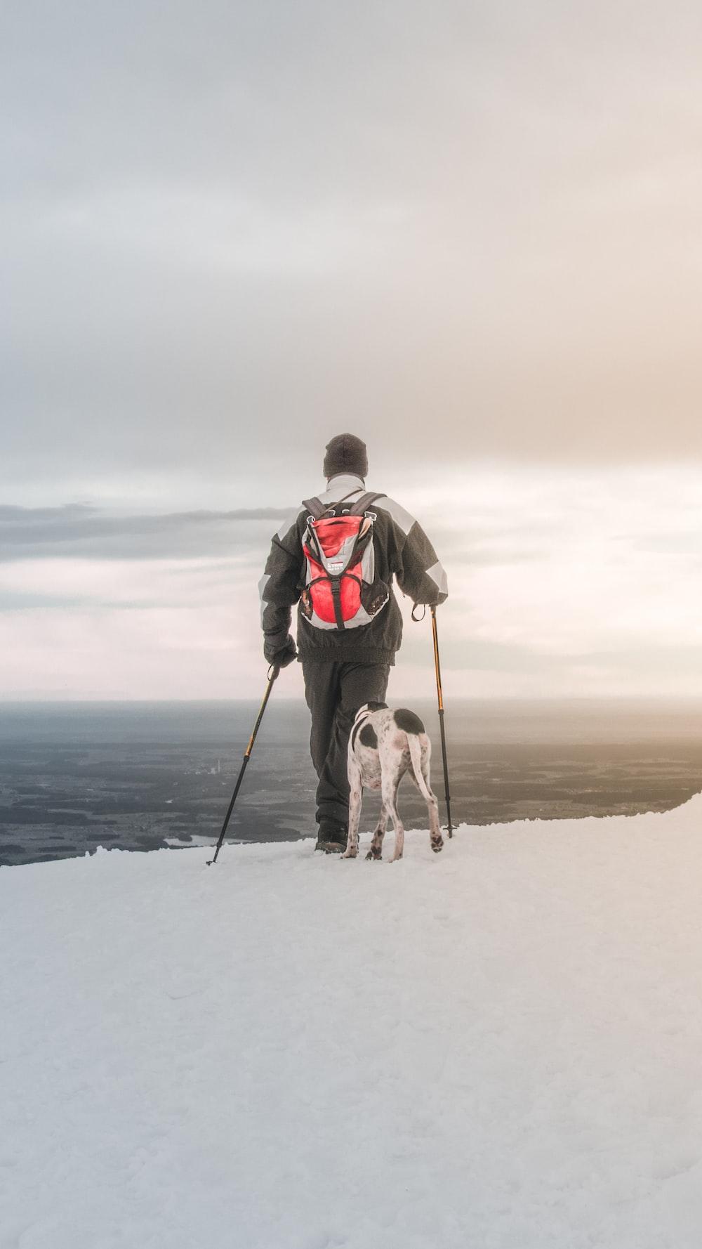 man hiking on frozen ground with dog