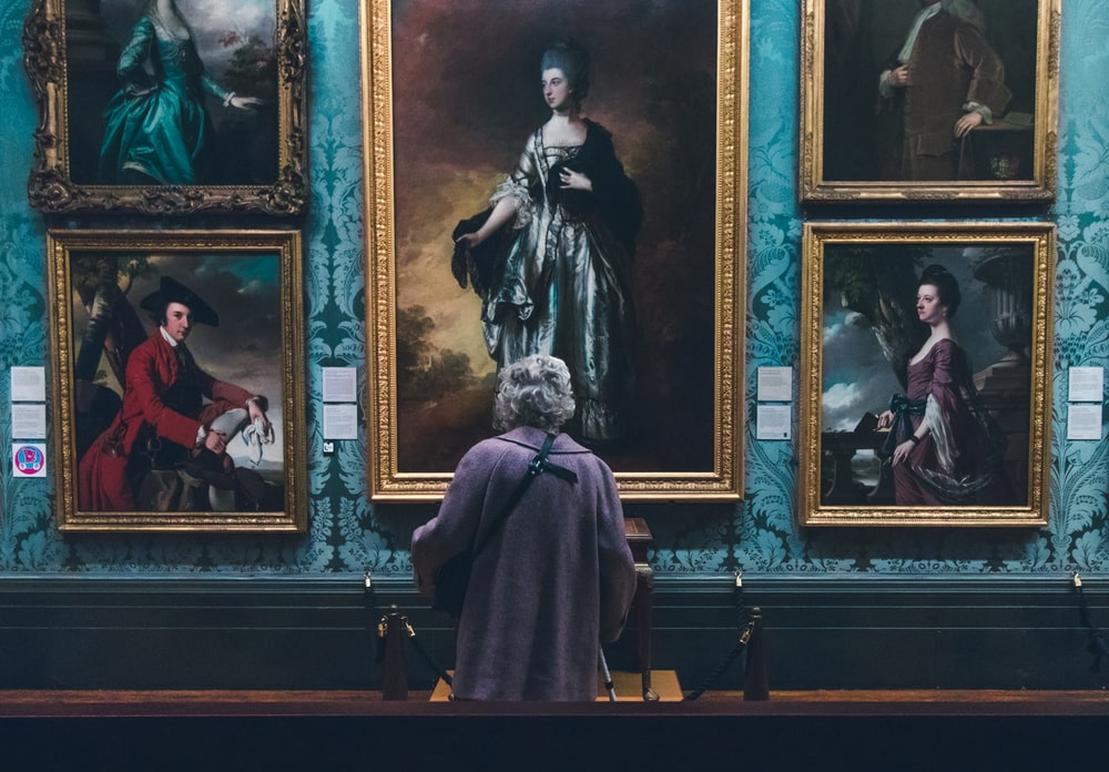 woman looking at painting on wall inside well lit room