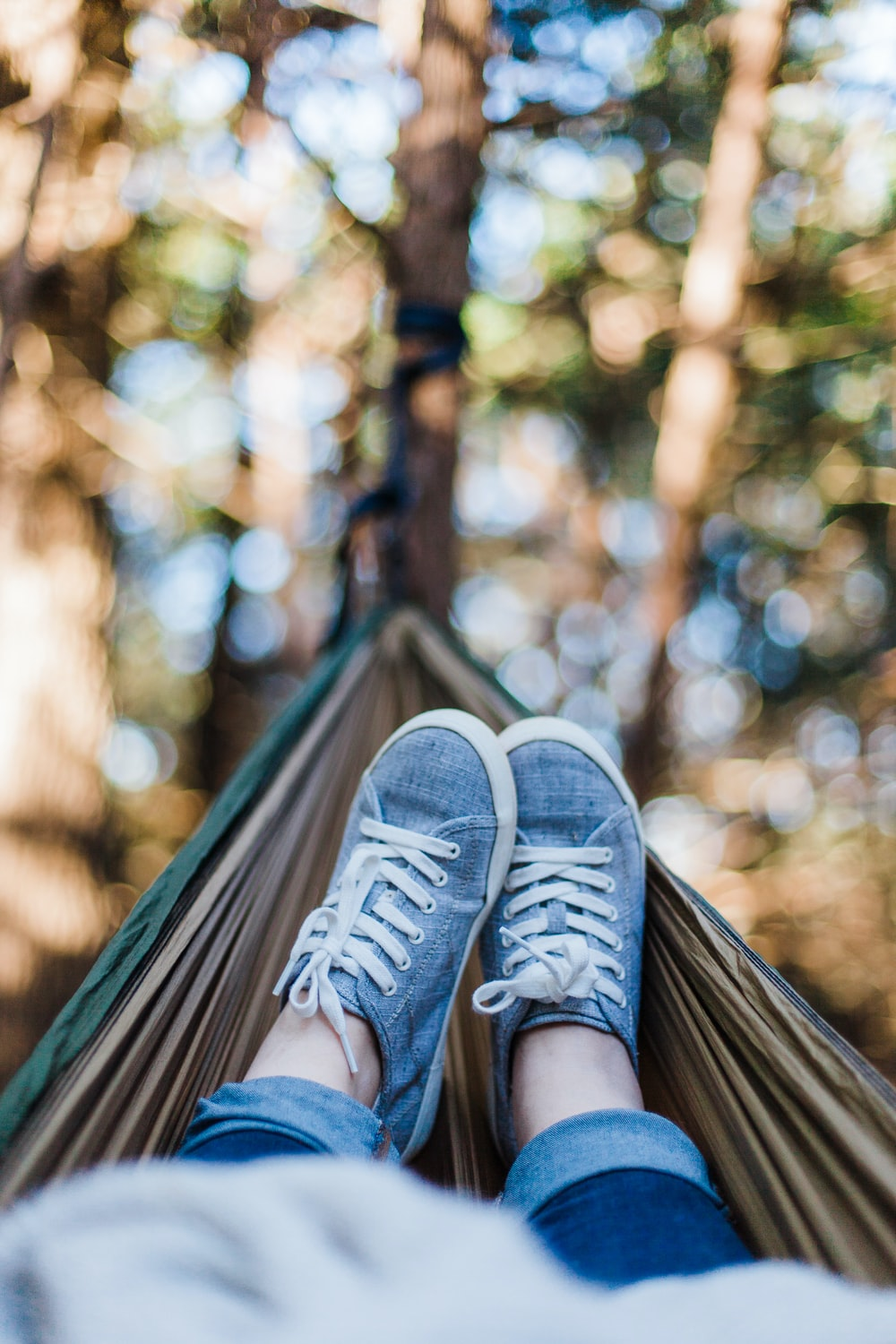 person laying down on brown hammock during daytime
