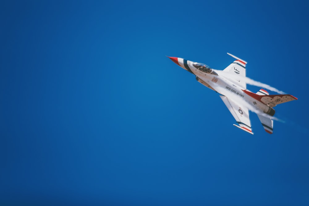 white and red jet plane hovering on sky at daytime