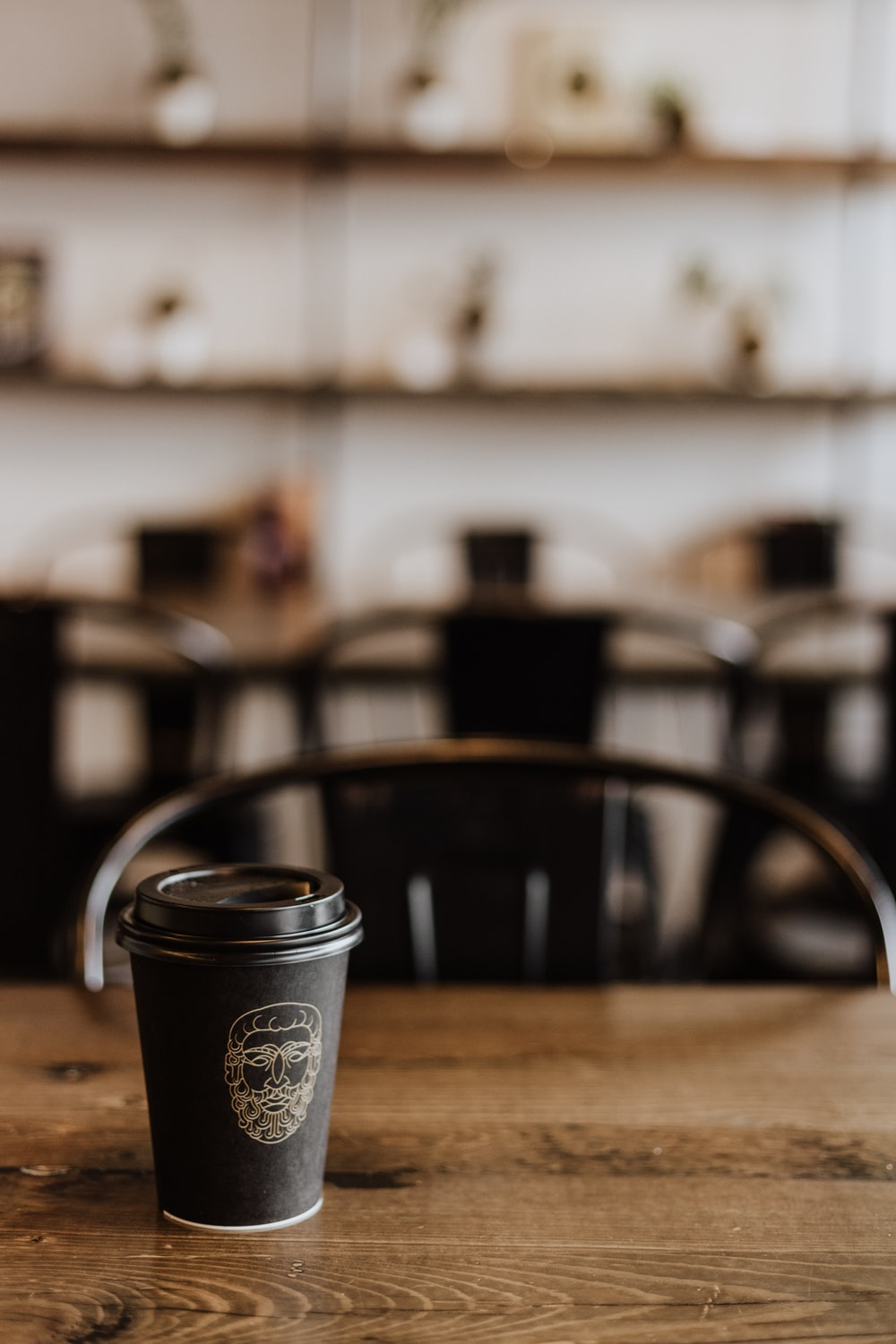 black disposable coffee cup on wooden table