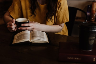 woman holding mug in front of book read teams background