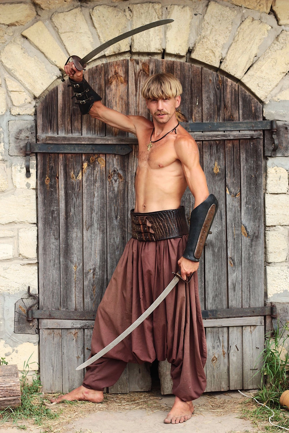 man holding two swords while standing in front of brown gate