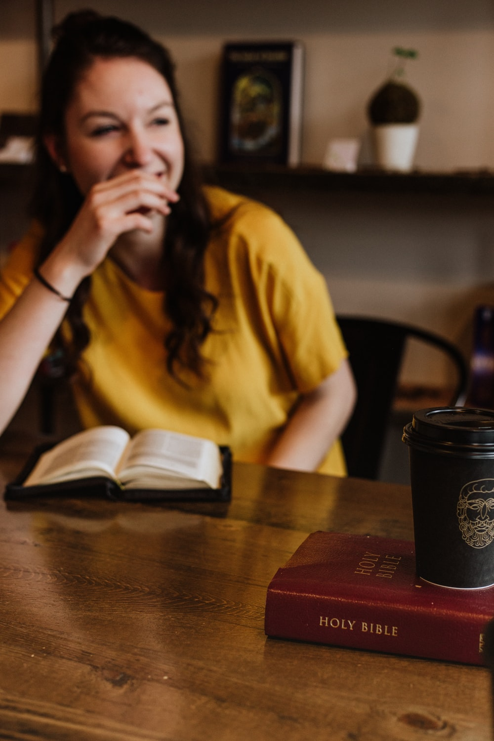 woman siting on chair near on holy bible