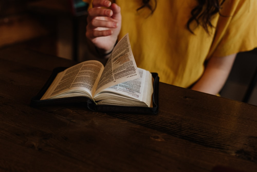person reading Bible on top of brown wooden table