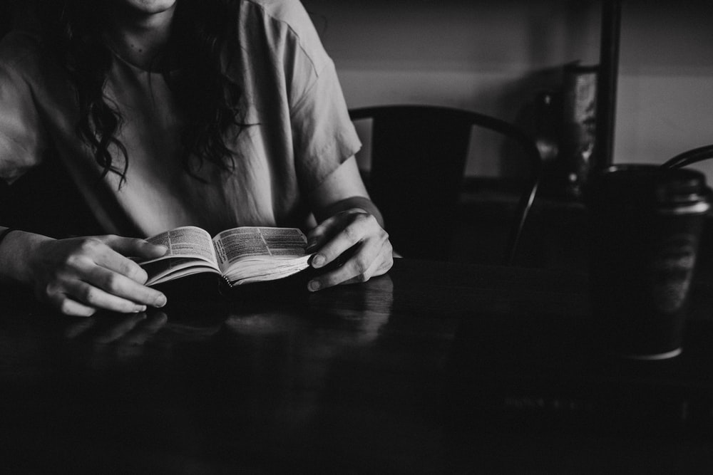 grayscale photo of woman reading a book on wooden table