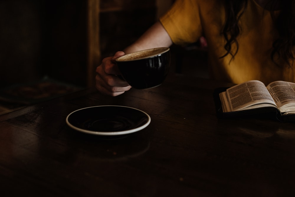 person holding black cup near saucer
