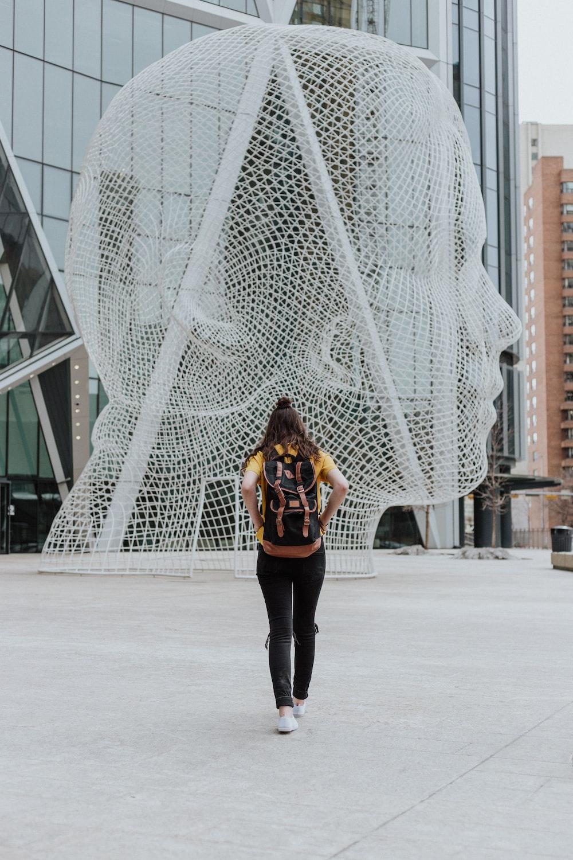 person walking toward face statue