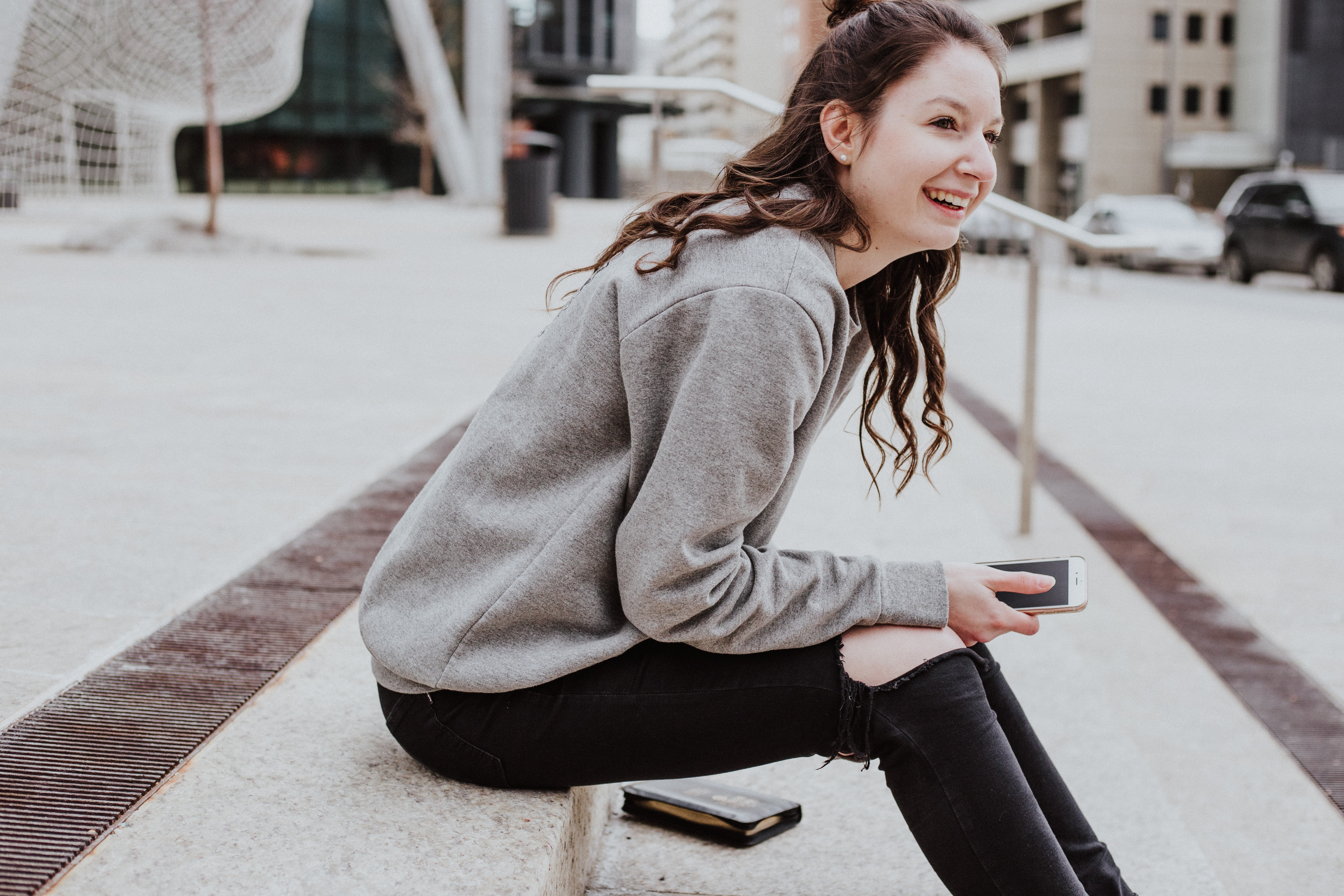 woman sits on sidewalk holding smartphone while smiling