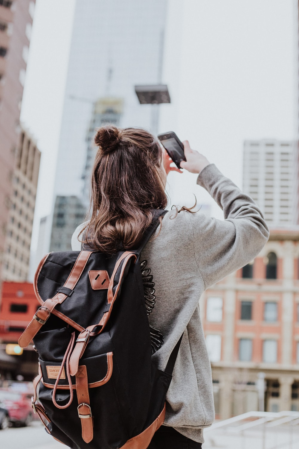 woman taking photo of high-rise building beside road
